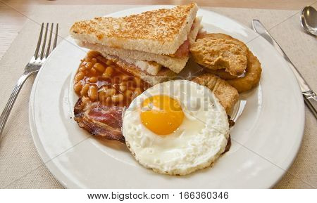 English breakfast - egg bacon beans and toast served on a plate