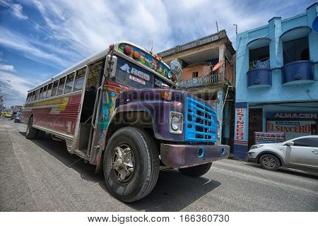 June 9 2016 Colon Panama: an old public transportation turned school bus drives through the street of the port town