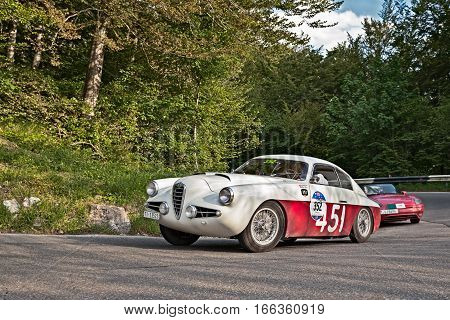 PASSO DELLA FUTA (FI) ITALY - MAY 21: driver and co-driver on a vintage sportscar Alfa Romeo 1900 SSZ Zagato (1955) in classic car race Mille Miglia on May 21, 2016 in Passo della Futa (FI) Italy