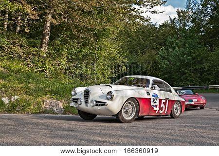 PASSO DELLA FUTA (FI) ITALY - MAY 21: driver and co-driver on a vintage sportscar Alfa Romeo 1900 SSZ Zagato (1955) in classic car race Mille Miglia on May 21, 2016 in Passo della Futa (FI) Italy