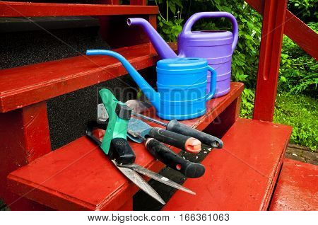Gardening tools - watering can shears hoe on wooden stairs