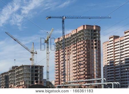 Three buildings under construction and three construction crane