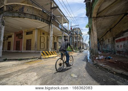 June 9, 2016 Colon, Panama: a local man is biking through the street in a poor neighbourhood of the port town