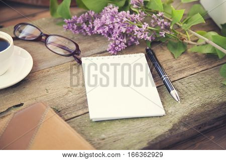 cup of coffee pen notepad papers glasses and flower on wooden table