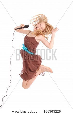 Happy young beautiful teenage girl jumping and singing with microphone isolated on white background
