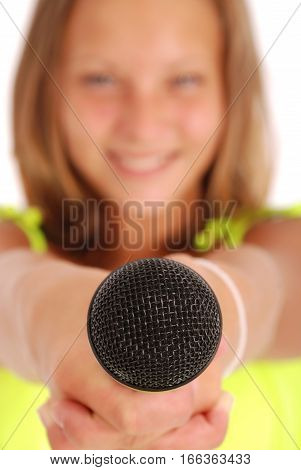 Teenage girl holding a microphone in front. Focus on the microphone. Isolated on white background