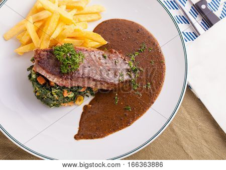 A nice dish of beef steak served with mashed potato,lemon, saute spinach and sauce on  background with wooden utensils.