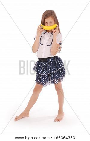 A young girl holds up a banana to her mouth imitating a smile. Isolated on white background