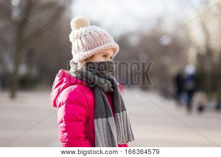 Closeup portrait of cute baby girl wearing knitted hat and winter jacket outdoors.