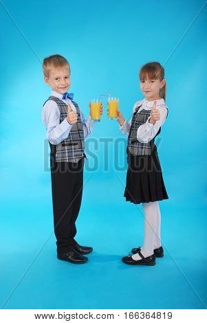 Girl and boy in school uniform drink juice - healthy diet. Photos on a blue background