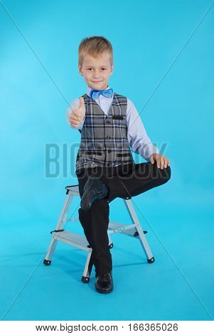 Schoolboy sitting on a stepladder and showing thumbs up. Photos on a blue background