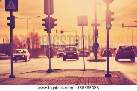 Cars moving on the road in city in early morning. View to the traffic with trafficlights and transport