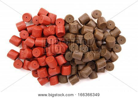 Brown with red pre-drilled halibut pellets for carp fishing isolated on white background with soft shadow