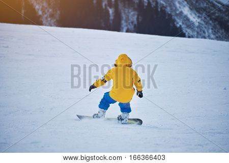 Snowboarder in bright yellow jacket and blue pants breaking with backside on snow slope at sunny winer day in mountain ski resort