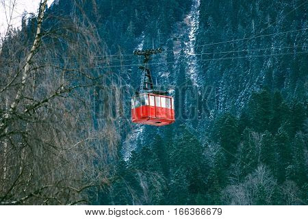Old vintage red cabin of air funiculair cable train moving in front of beautiful winter forest with many blue pines