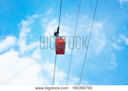 Beautiful vintage red aerial cableway train cabine moving across, isolated on bright blue sky