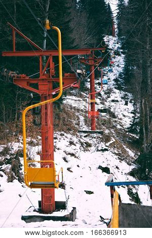 Vertical shot of beautiful old small ski lift with colored chairs, moving through winter forest in mountains