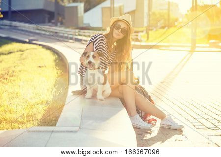 Beautiful Hipster Girl with her Dog in the City Park. Smiling Woman with Pet Outdoors at Sunset. Trendy Fashion Female in Summer. Toned and Filtered Photo with Bokeh. Modern Youth Lifestyle Concept.