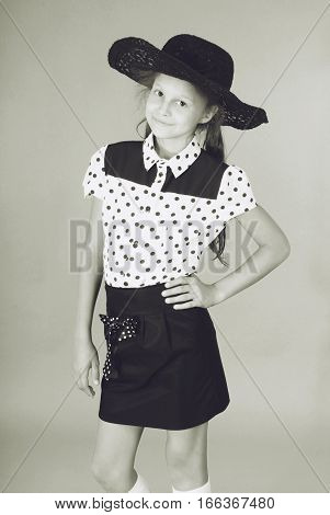 Beautiful young girl in black hat on his head. Black and white image