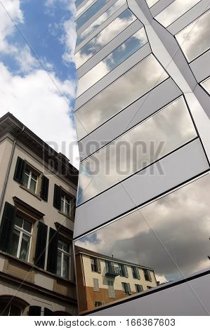 Fragments of old and modern buildings in the reflection in Swiss city.