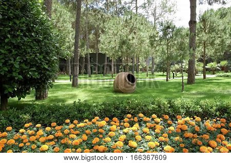 Kemer, Turkey - May 31, 2015: Pines, amphora and yellow flowers in the garden of the hotel Paloma Renaissance Antalya Beach Resort in Turkey.