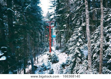 Beautiful vintage grunge ski lift with pastel colored chairs, moving through winter pine forest covered in fresh snow in mountains