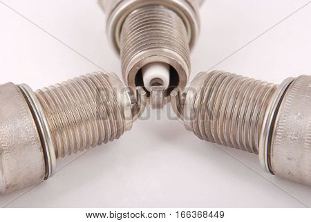 Three new spark plug on a gray background