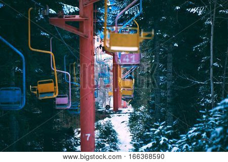 Close focus shot of many pastel colored chairs of retro grunge ski lift, moving through winter pine forest covered in fresh snow in mountains