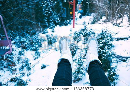 POV shot of women legs weared black jeans and white shoes in chair of small grunge ski lift moving through winter forest covered in snow