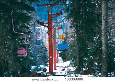 Row line of many pastel colored chairs of retro grunge ski lift, moving through winter pine forest covered in fresh snow in mountains