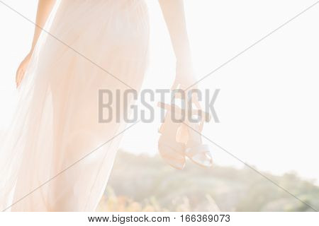 bride in wedding dress holding a shoes at sunset. fine art wedding photography