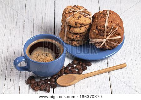Cup of hot coffee and chocolate cookies tied with ribbon in plate on white wooden table