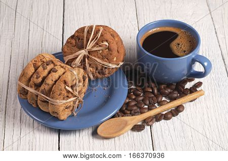 Cup of hot coffee and chocolate cookies tied with on white wooden table