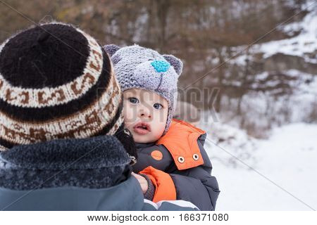 Family of father and his son outdoors on beautiful winter snowy day. Portrait of happy father and his adorable little son. Concept of friendly family. Cute boy with dad playing outdoor in winter.