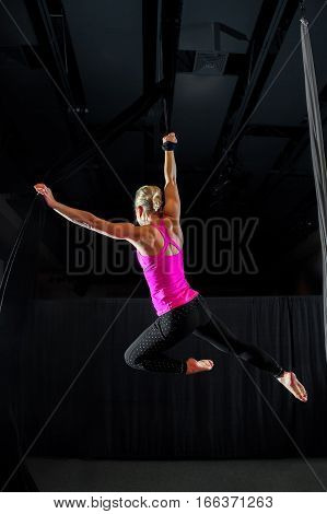 An aerialist in bright pink hanges from a black silk in a belay loop teardrop arabesque pose against a mostly balck background. Her back is shown and is very muscular.