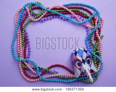 Mardi Gras beads and mask making a frame with copy space on a purple background