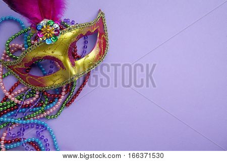 Festive, colorful group of mardi gras or carnivale mask on a purple background. Venetian masks.