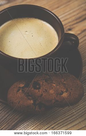 Cup of coffee and cookies on wooden vintage board background macro