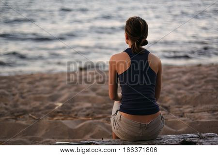 Back view of attractive woman in dark top, sitting on big wooden beam next to water of evening lake, pleasured with warm chill evening