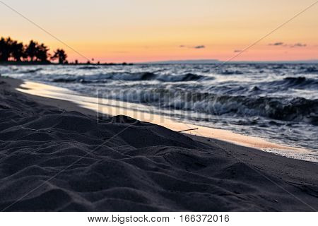 Low light landscape shot of empty chilly lake beach with sand during sunset and twilight at summer evening time. Outdoor camping in nature