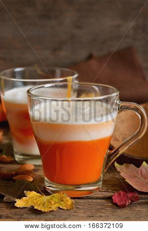 Home latte with milk almonds and pumpkin on a wooden background