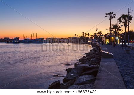View over the seafront of the city Paphos in Cyrpus. Palm silhouettes, boats in the water and golden sunset over the sea with dramatic cloudy sky.