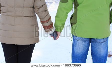 Woman in winter coat with white fur and grey knitted mittens and man in green sports jacket holding together at snowy background.