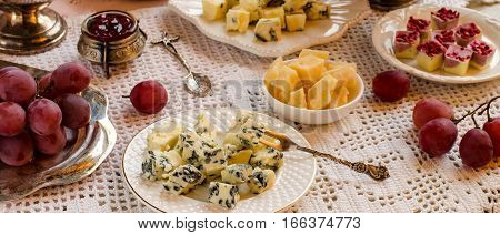 A Beautiful Table Setting With Cheeses And Desserts.
