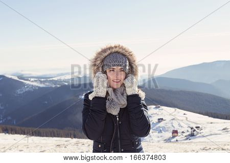 Winter view of a young woman admiring mountain landscape. Film filter