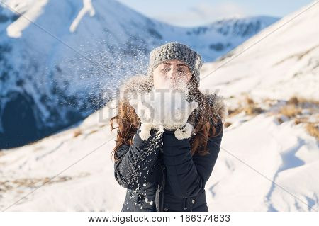 Winter portrait of a young woman blowing snow, at the mountain