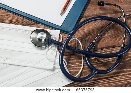Doctors wooden table with tablet stethoscope and other stuff