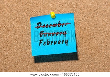 February beginning concept. Inscription with strikeout December and January month, written on sticker pinned at board.