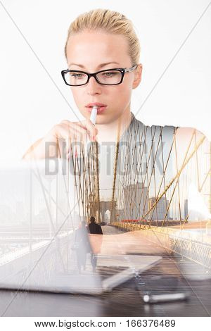 Business woman wearing black glasses, holding pen in hand, checking some information on her laptop computer in office, of thougths, day dreaming about afterwork leisure activities in New York city.