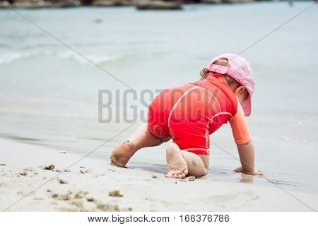 Stubborn child crawling towards water on beach during summer holidays